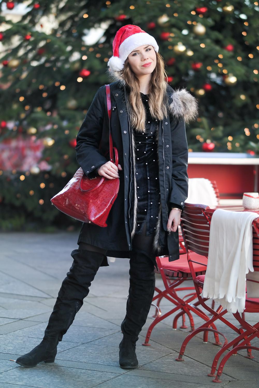 weihnachtslook-weihnachts-outfit-schwarzer-Parka-gefüttert-Fake-Fur-Overknee-Stiefel-Mollerus-Tasche-Weihnachtsmütze-grüner-Tannenbaum-geschmückt