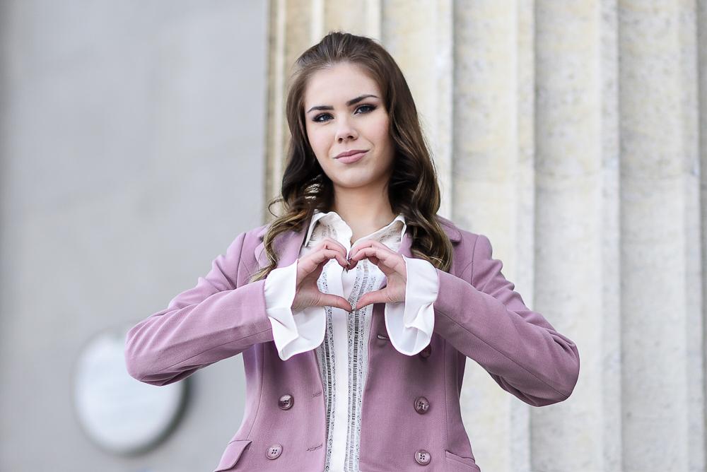 Valentinstag Look Outfit-mädchenhaft-romantisch-rosa Mantel Schösschen-Rüschen-weiße Bluse Trompetenärmel-Locken-lockige Haare-hohe Schuhe-High Heels-Herz