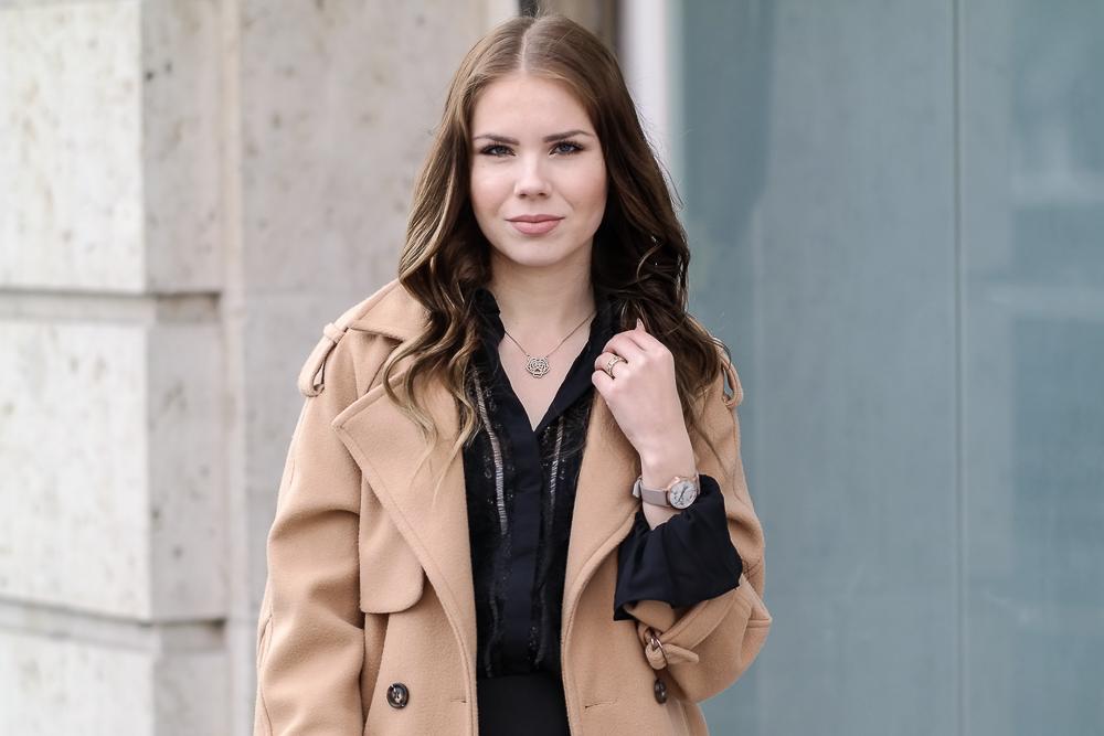 Mantel-Halbkörper-schwarze-Bluse-Cluse-Uhr-Kette-Tigerkopf-lockige-Haare