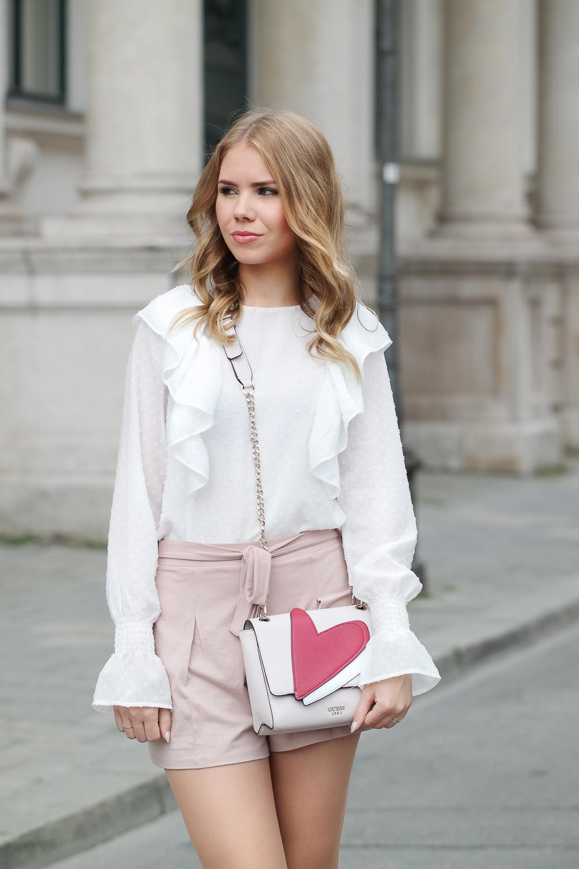 Fashion Blog München Bluse Rüschen Trompetenärmel-rosa Shorts-Guess Tasche-Halbkörper Foto