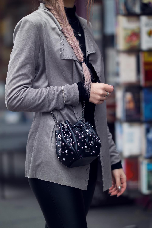 Rockiger Look-Halbkörper-rosa Haare-Frischgrätenzopf-Wildlederjacke-Lederhose-Karl Lagerfeld Beuteltasche