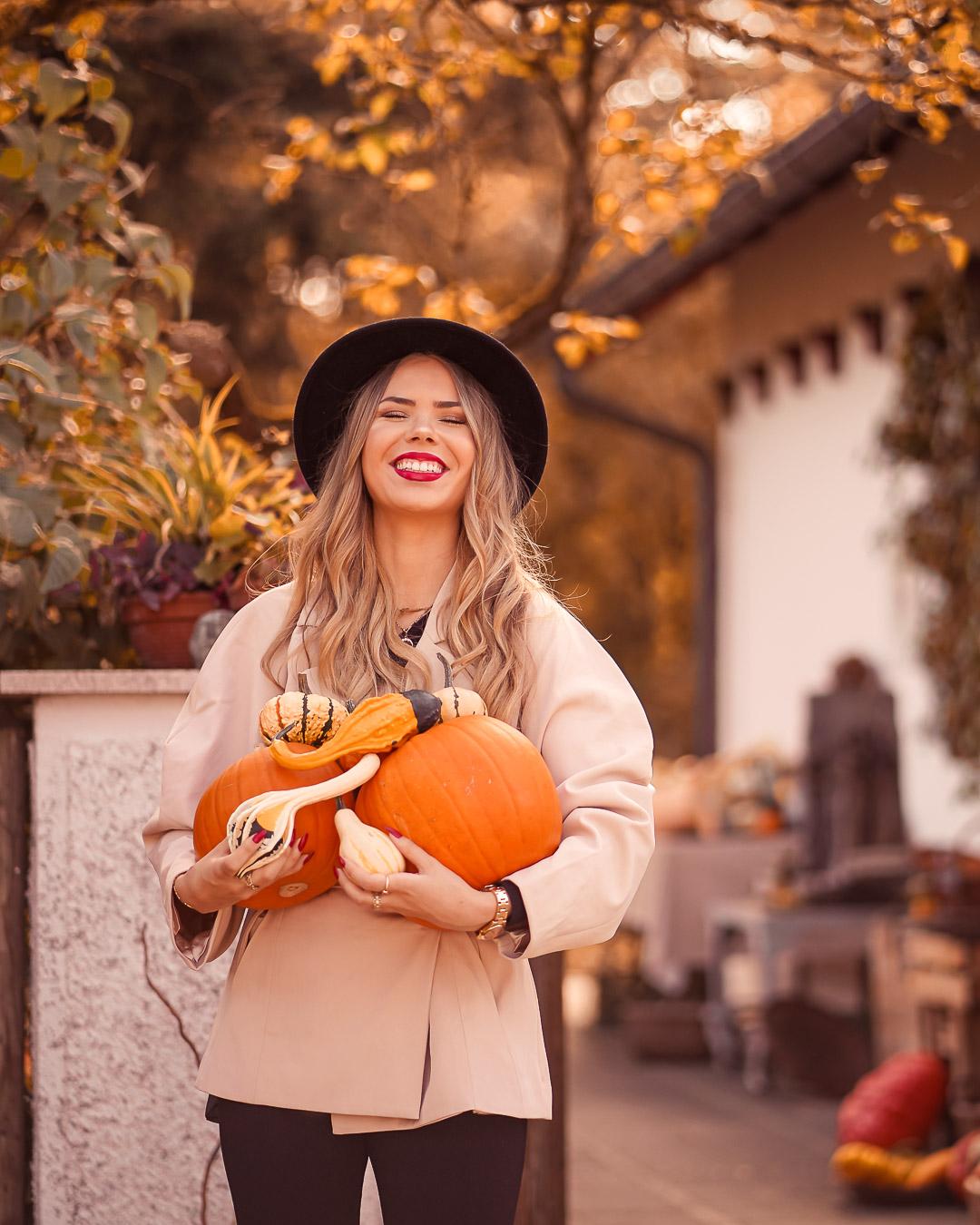 Fröhliches Herbstfoto mit Kürbissen im Arm