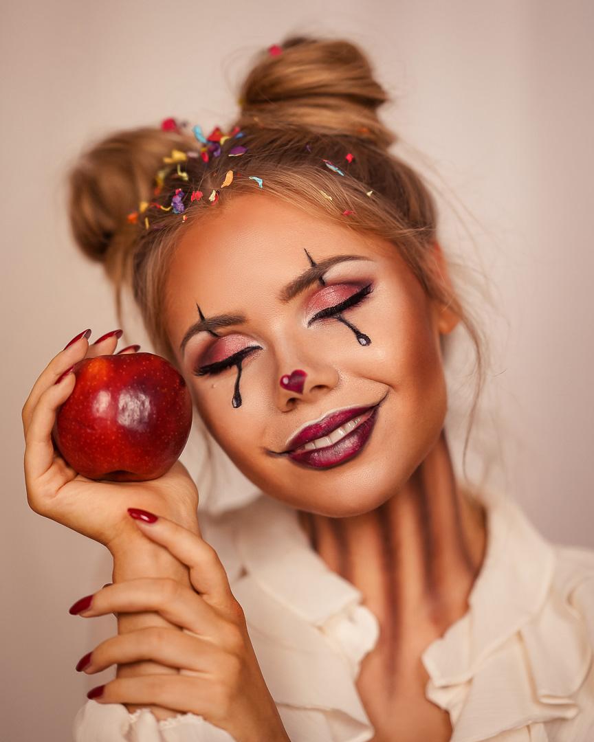 Portrait Halloween Makeup Clown mit Apfel in der Hand