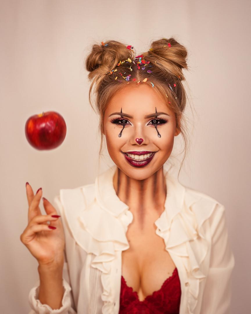 Lachender Halloween Makeup Clown mit werfenden Apfel